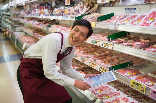 スーパーで仕事をする男性店員の写真