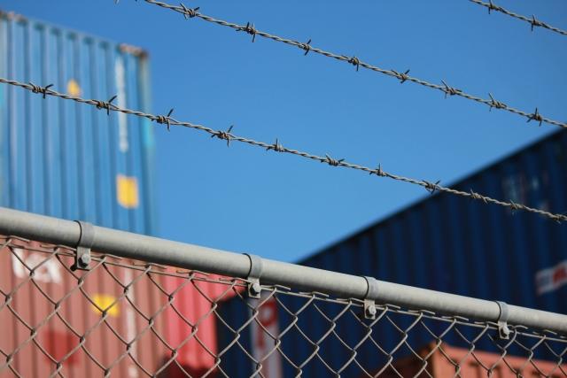 有刺鉄線がついたフェンスの写真