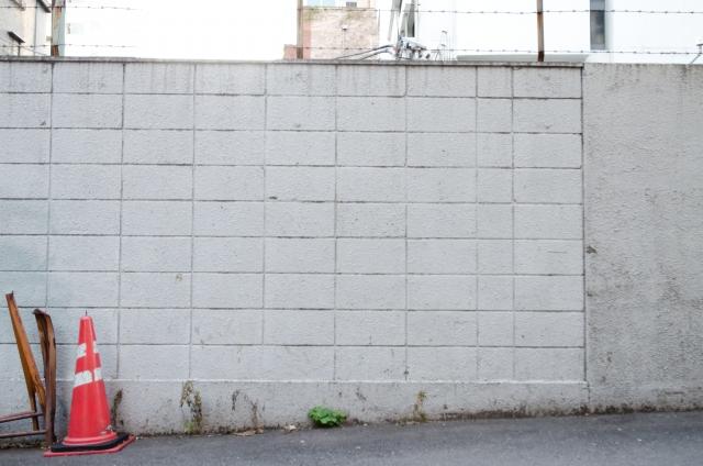 有刺鉄線がついたブロック塀の写真