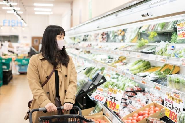 マスクを付けてスーパーで買い物をする女性の写真